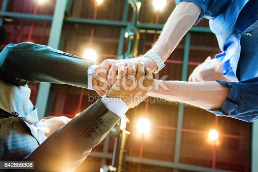 Two businessmen shaking hands from below with an illuminated ceiling background. They are using both hands for extra emphasis.