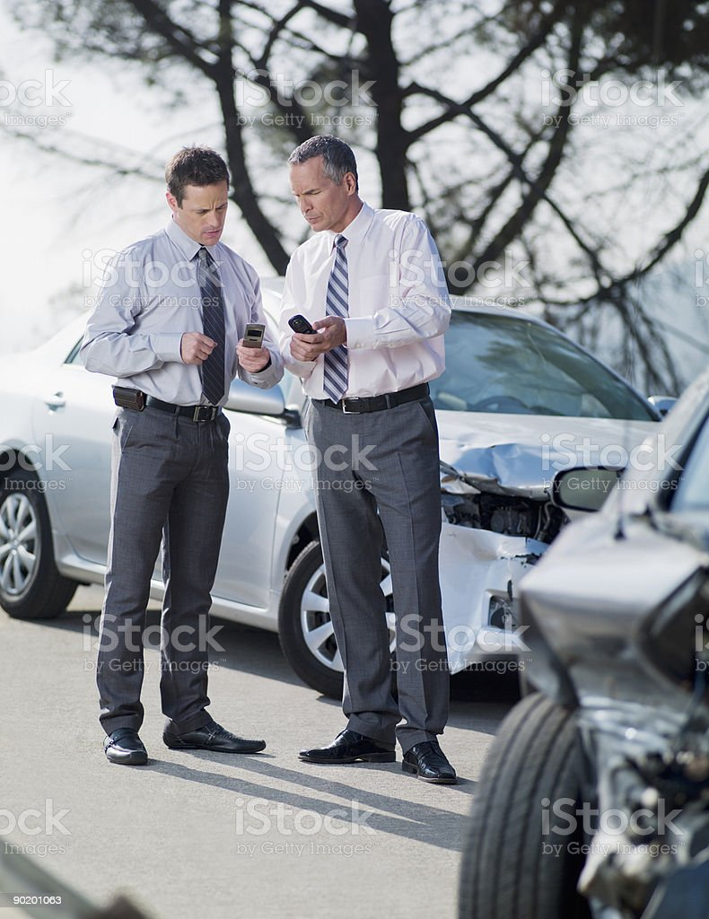Two businessmen exchanging information about damaged cars stock photo