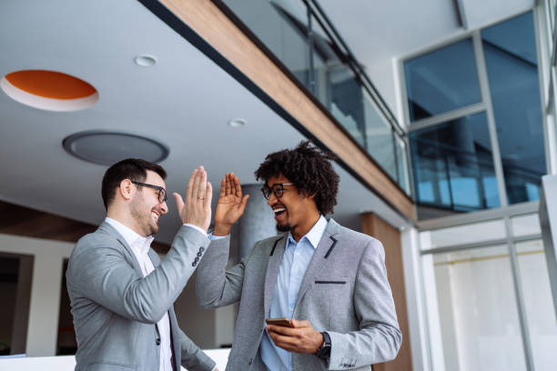 Two businessmen giving each other high-five stock photo