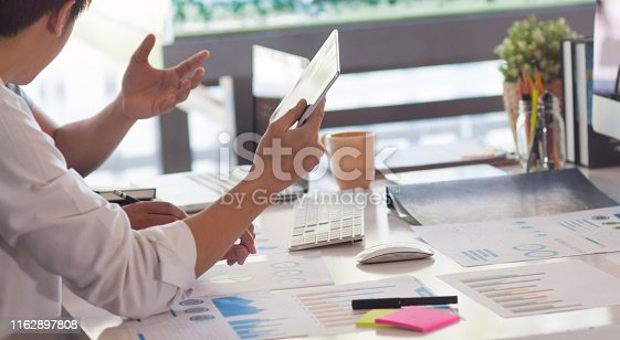 1068752548 istock photo Two businessmen hold a tablet and talk about marketing and business profits. 1162897808