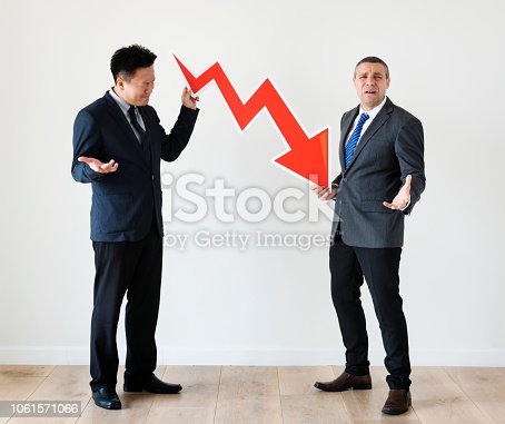 istock Two businessmen holding the arrow down 1061571066