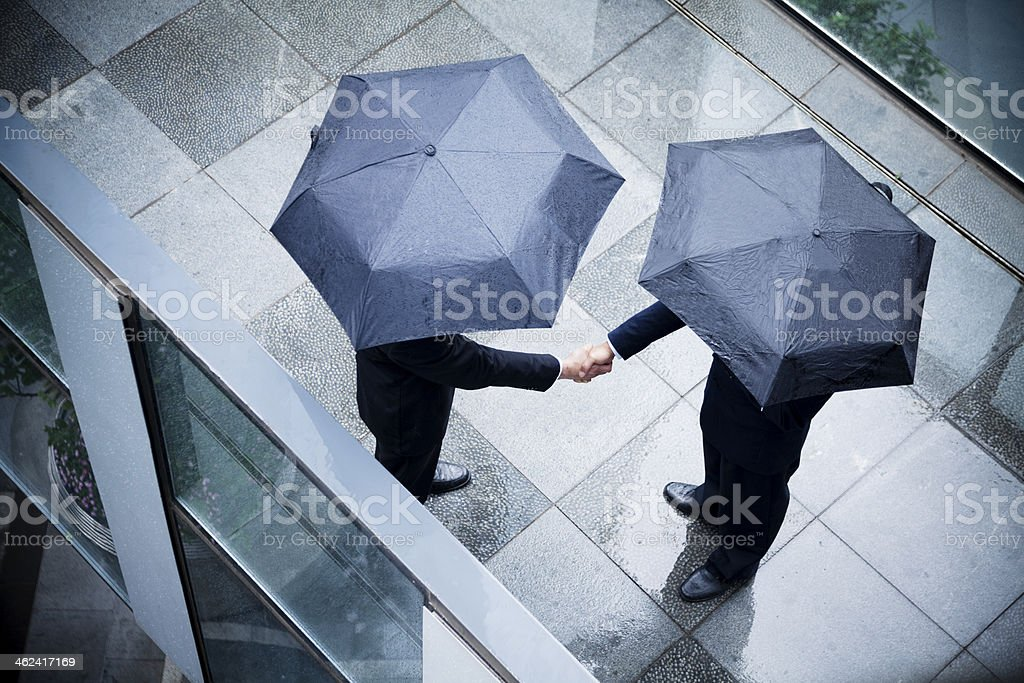 Two businessmen holding umbrellas and shaking hands outside royalty-free stock photo