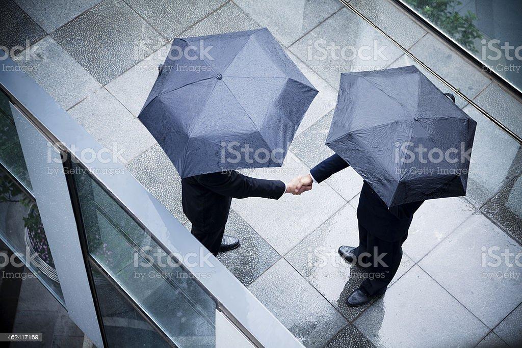 Zwei Geschäftsleute halten Sonnenschirme und beim Händeschütteln im Regen – Foto