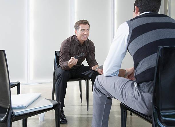 Two businessmen in boardroom talking stock photo