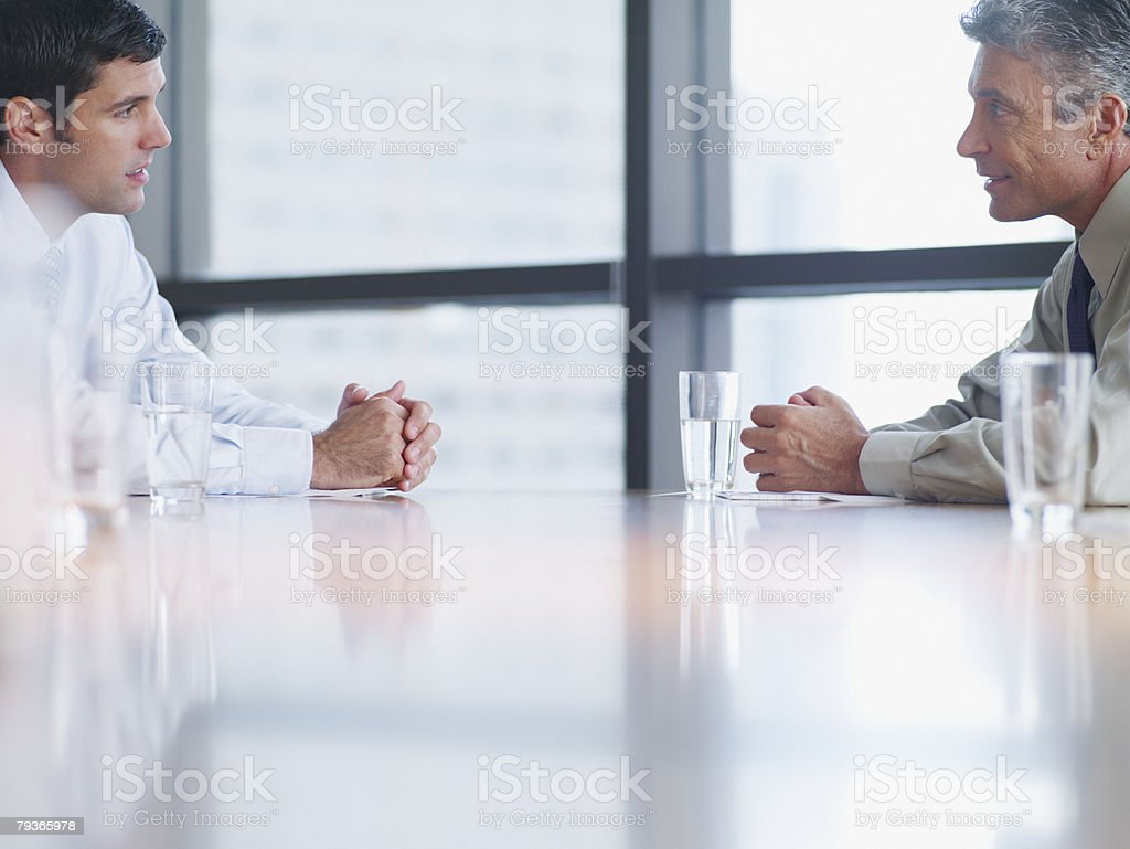 Two businessmen in boardroom with paperwork stock photo