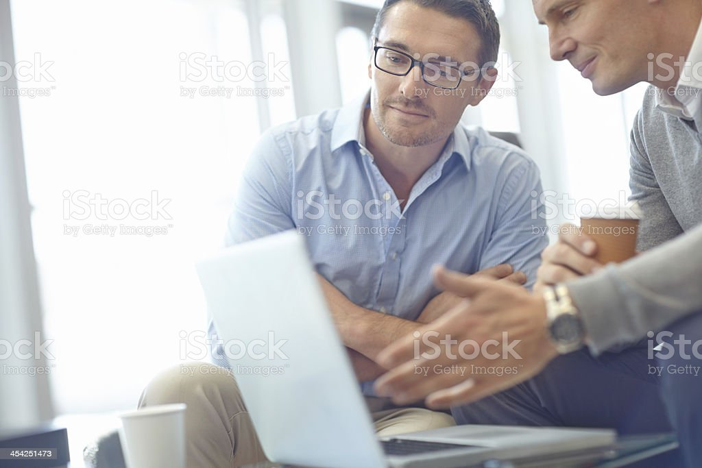 Two businessmen in discussion near a laptop stock photo