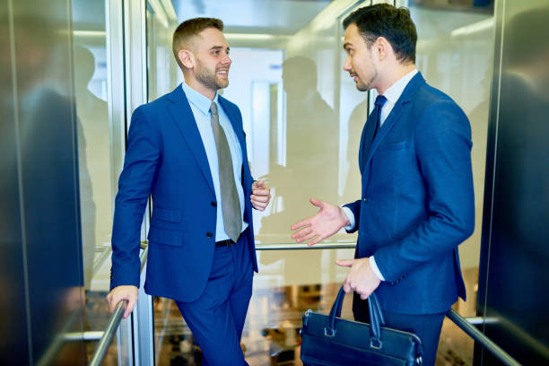 two businessmen in elevator - ascensore foto e immagini stock