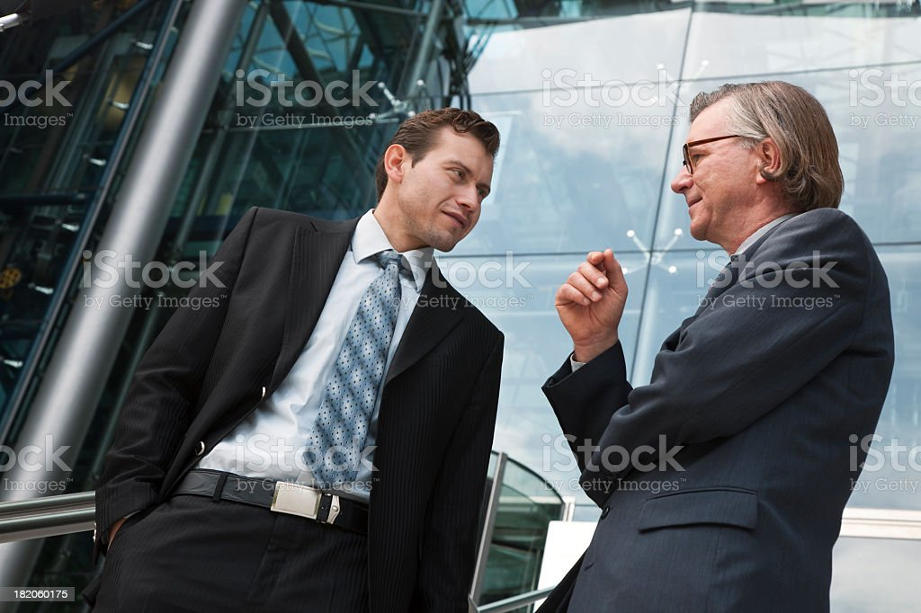 Two Businessmen in Front of Glass Office Building royalty-free stock photo