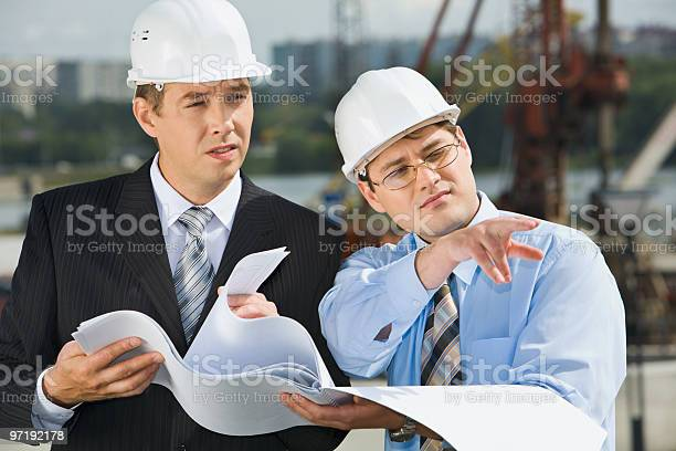 Two Businessmen In Hard Hats Holding Plans Meet Onsite Stock Photo - Download Image Now