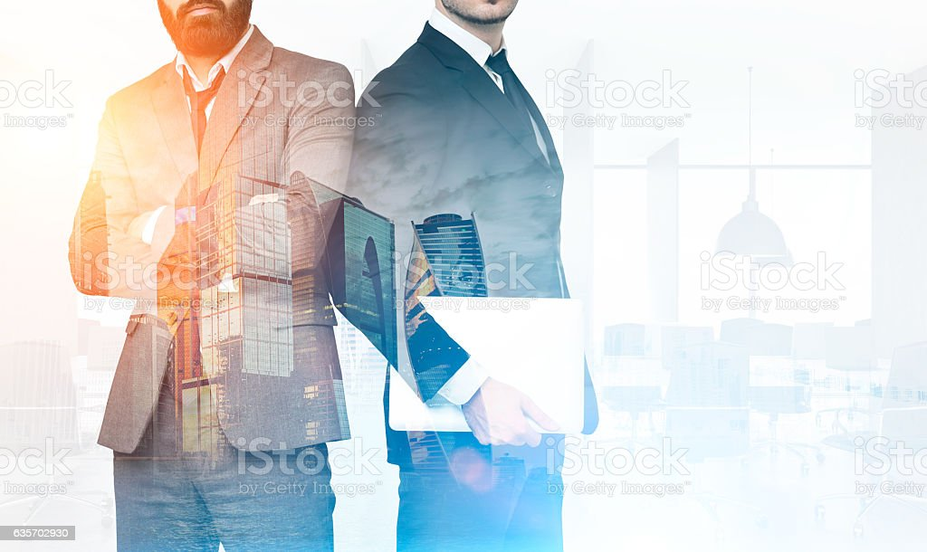 Two businessmen in office with skyscrapers, toned royalty-free stock photo