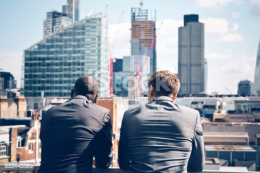 Back view of two businessmen - caucasian and afro american - standing outdoor and looking at city scape.