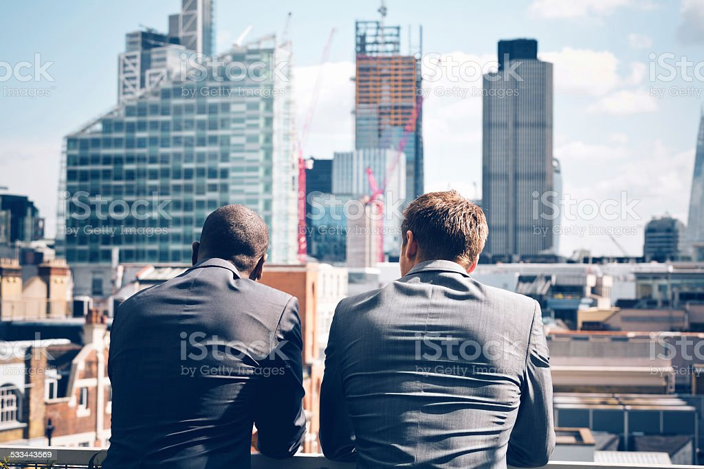 Two businessmen looking at city scape stock photo
