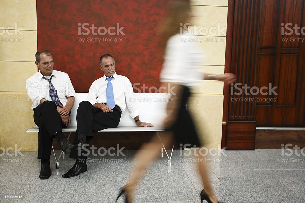 Two businessmen looking at woman's legs stock photo