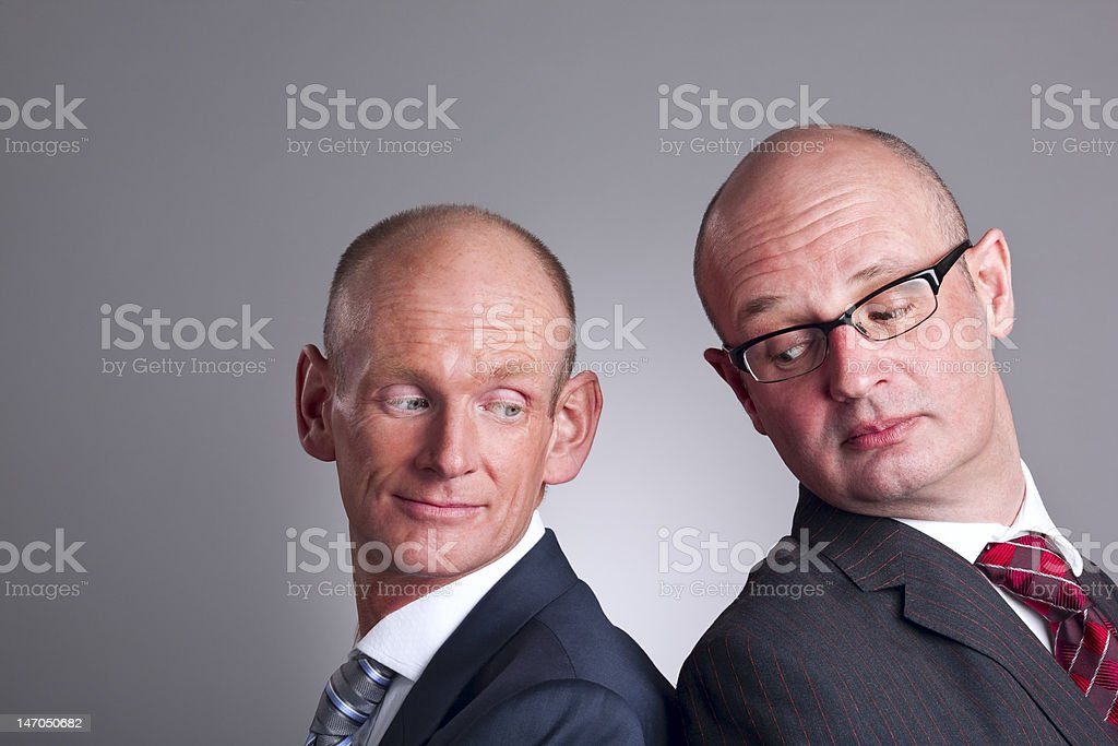 Two businessmen looking over shoulder stock photo