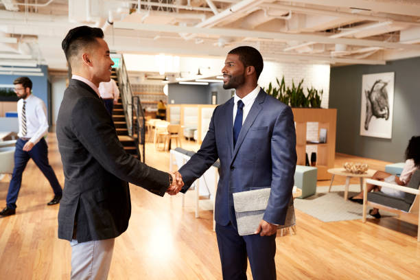 Two Businessmen Meeting And Shaking Hands In Modern Open Plan Office Two Businessmen Meeting And Shaking Hands In Modern Open Plan Office design occupation stock pictures, royalty-free photos & images
