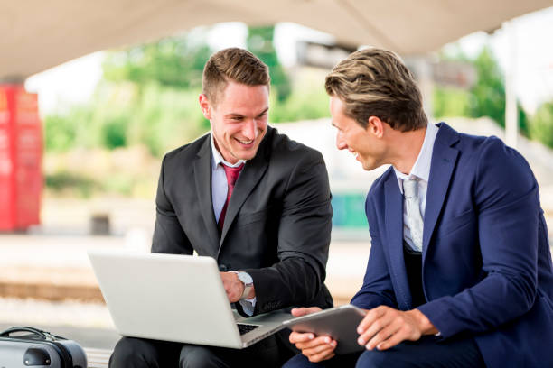 two businessmen on a train station using laptop and digital tablet - leaving partnership corporate business sitting stock photos and pictures