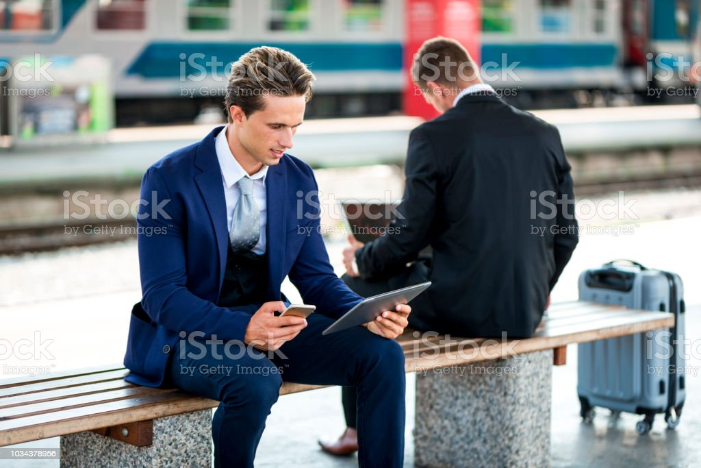 Two businessmen on a train station using laptop and digital tablet stock photo