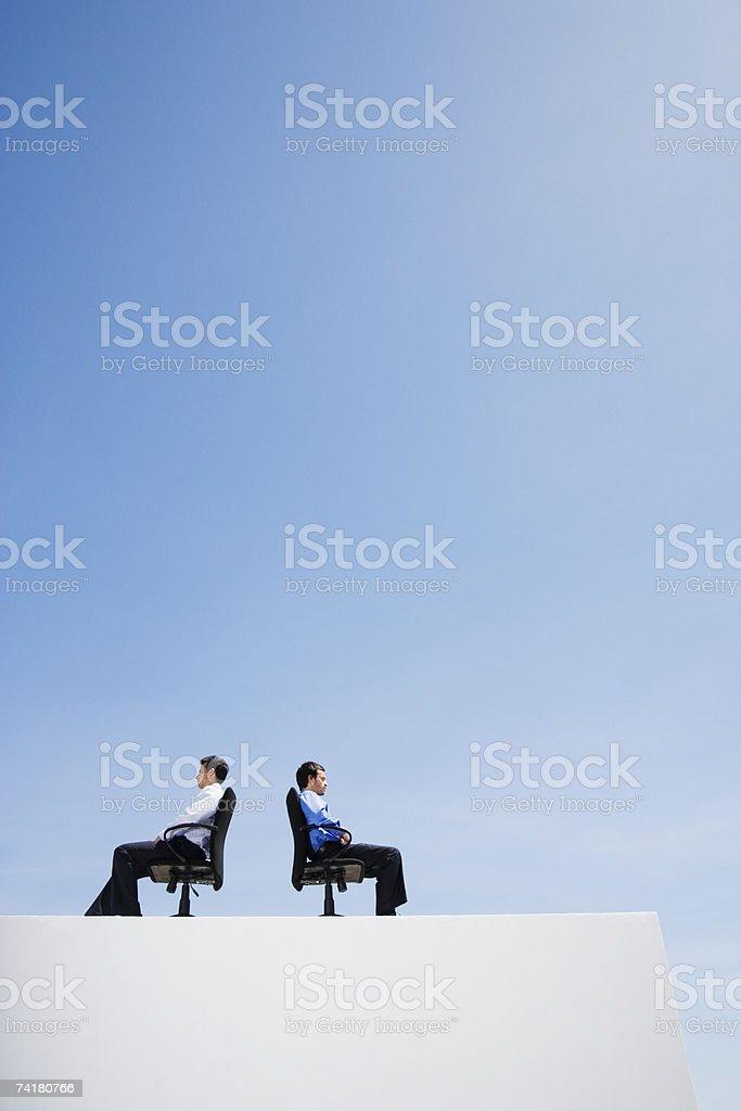 Dois empresário na parede com escritório e cadeiras Costas Com Costas foto de stock royalty-free