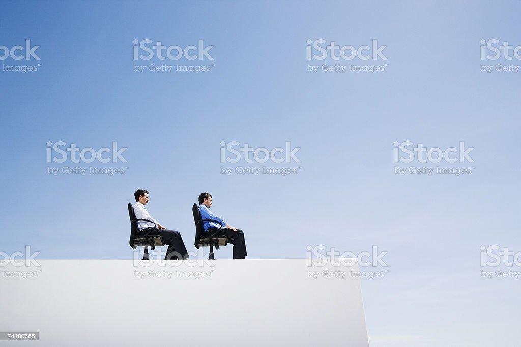Dois empresário na parede com escritório e cadeiras em uma linha foto de stock royalty-free