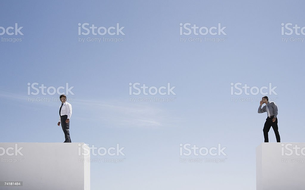 Two businessmen on walls outdoors with large gap stock photo