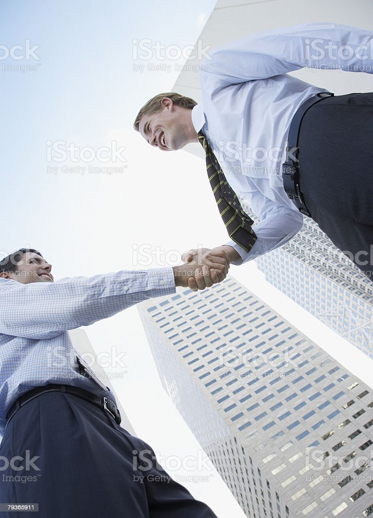 Two businessmen outdoors shaking hands 免版稅 stock photo