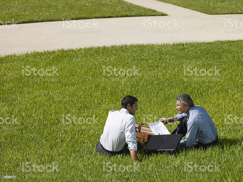 Two businessmen outdoors sitting in grass with paperwork royalty-free stock photo