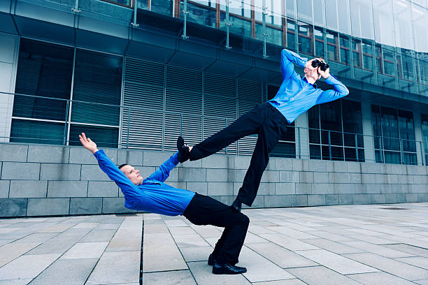 Two businessmen performing an acrobatic stunt together stock photo