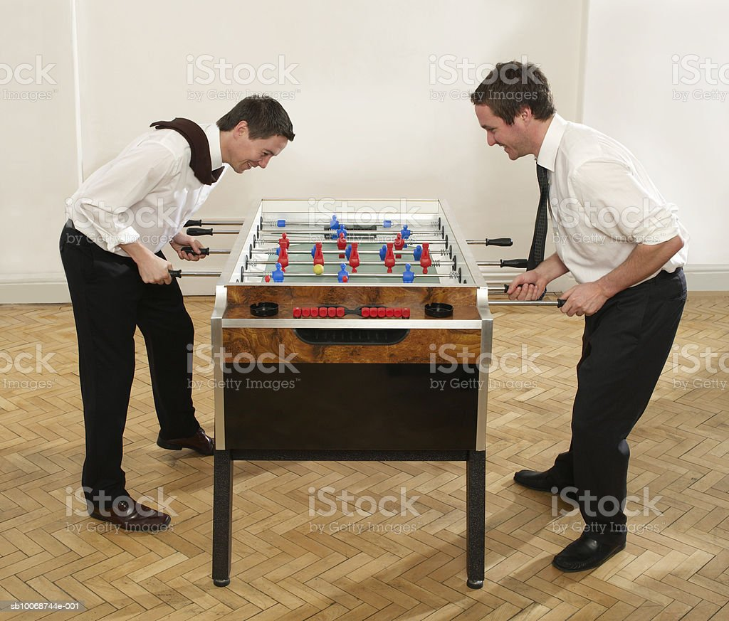 Two businessmen playing table football, side view foto de stock libre de derechos