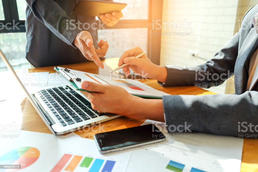 Two businessmen pointing at a graph to analyze data. royalty-free stock photo
