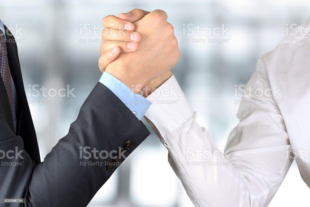 Zwei Geschäftsleute halten einander die Hände auf Vorwärts Hintergrund – Foto