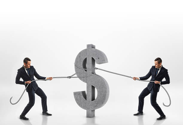 Two businessmen pulling big concrete 3d dollar sign with ropes stock photo