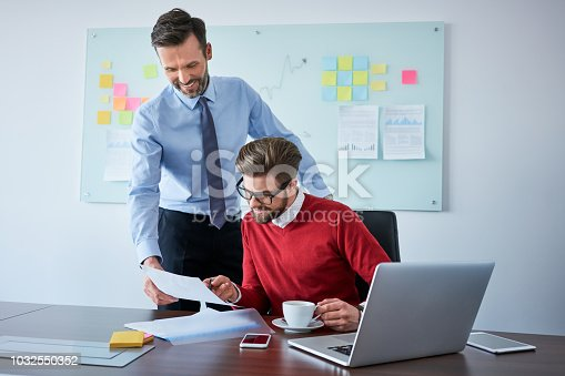 istock Two businessmen reading contract documents at corporate office 1032550352