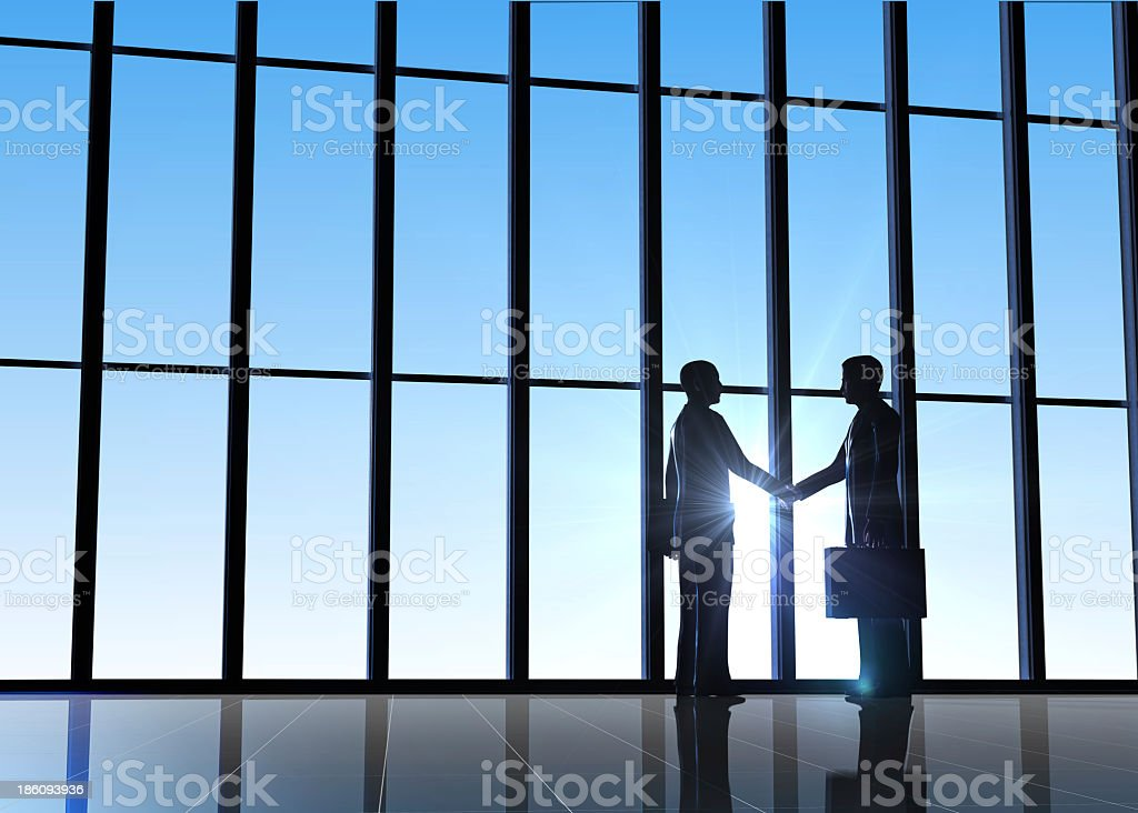Two businessmen shaking hands in a glass building royalty-free stock photo