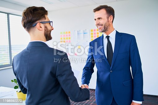 859896852istockphoto Two businessmen shaking hands in office after successful deal 1198592270