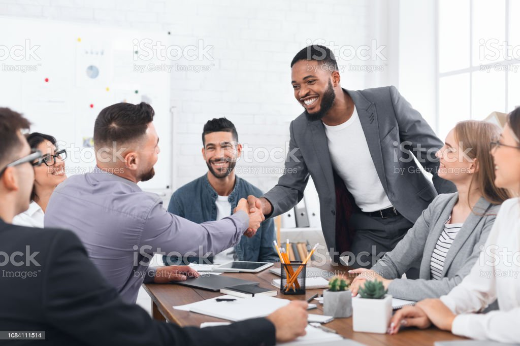 Two businessmen shaking hands, sitting at desk stock photo