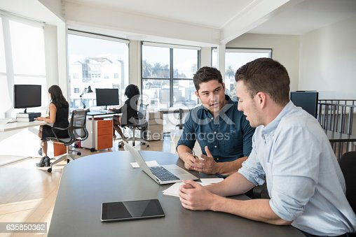 istock Two businessmen sitting at desk in office with laptop 635850362