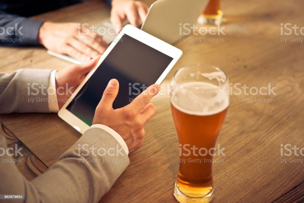 Two businessmen sitting in the pub, having beer and using computers Two businessmen sitting in the pub, having beer and using digital tablet and laptop. Unrecognizable people, close up of hands. Adult Stock Photo