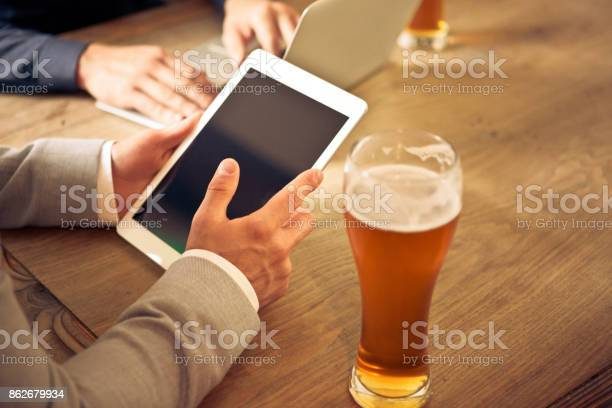 Two Businessmen Sitting In The Pub Having Beer And Using Computers Stock Photo - Download Image Now