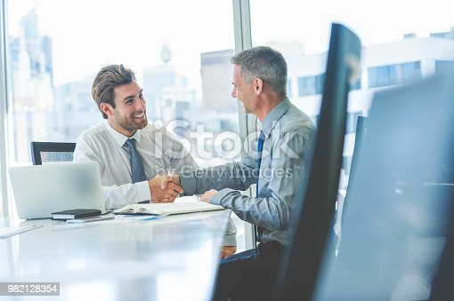 Two businessmen smiling and happy shaking hands in a meeting. There is a laptop on the board room table. The handshake is done sitting down. Both are dressed in formal business attire. The city can be seen through the window