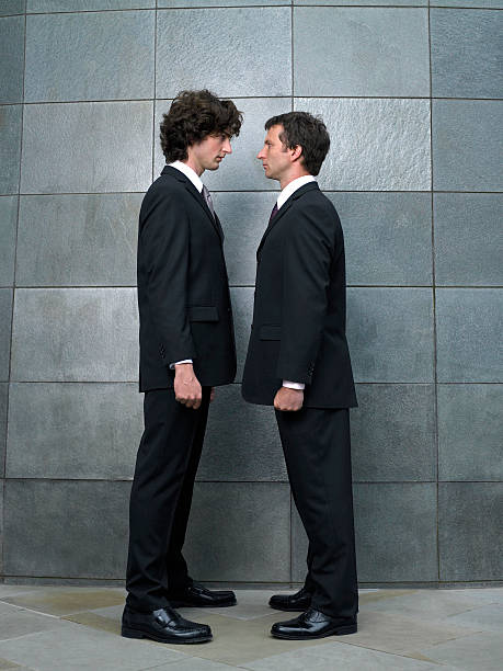 Two businessmen standing face to face, side view stock photo