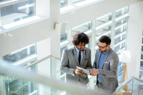 Two businessmen standing on staircase and using digital tablet stock photo