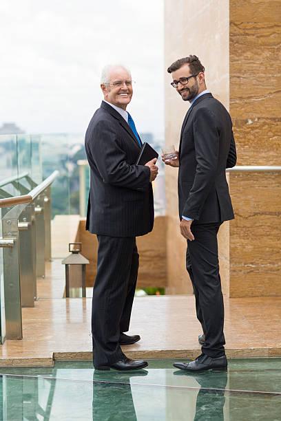 two businessmen standing outside office - leitungswasser trinken stock-fotos und bilder