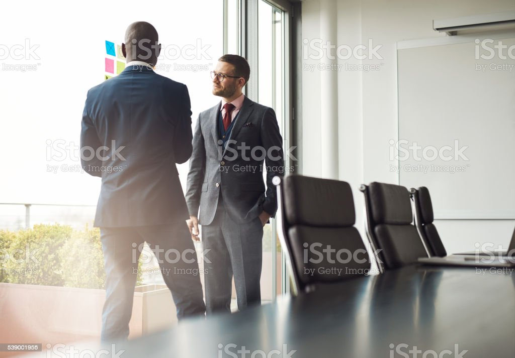 Two businessmen standing talking together stock photo
