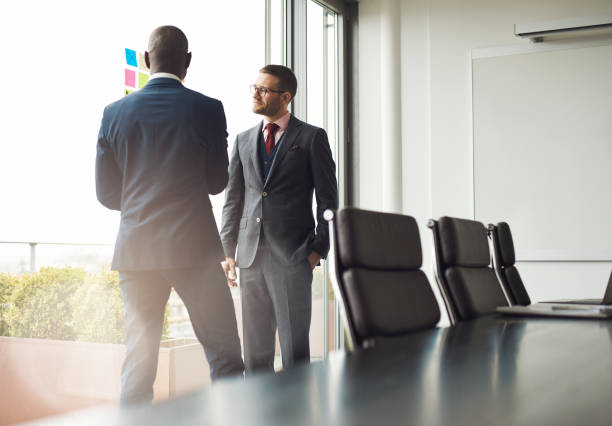 Two businessmen standing talking together Two multiracial businessmen standing talking together in front of a window in a conference room, view over the table with sun flare through the window governing board stock pictures, royalty-free photos & images
