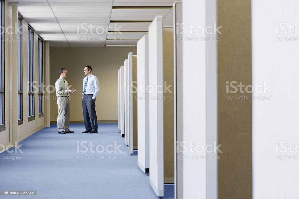 Two businessmen talking besides office cubicle foto de stock libre de derechos
