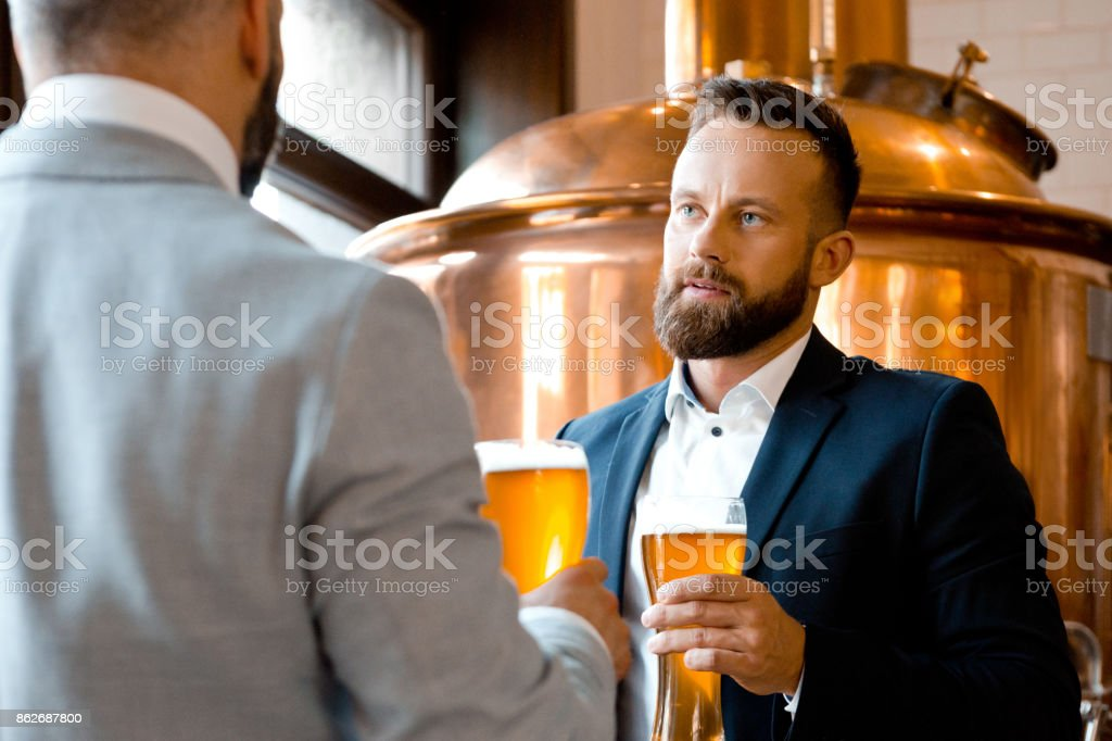 Two businessmen talking over beer in the microbrewery Two businessmen talking over beer in the microbrewery. Copper vat in the background. Adult Stock Photo