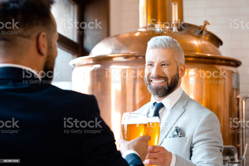 Two businessmen toasting with beer in the microbrewery Two businessmen toasting with beer in the microbrewery. Copper vat in the background. Adult Stock Photo
