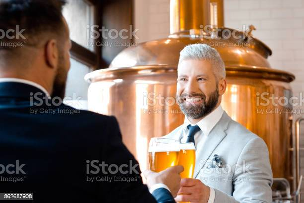 Two Businessmen Toasting With Beer In The Microbrewery Stock Photo - Download Image Now