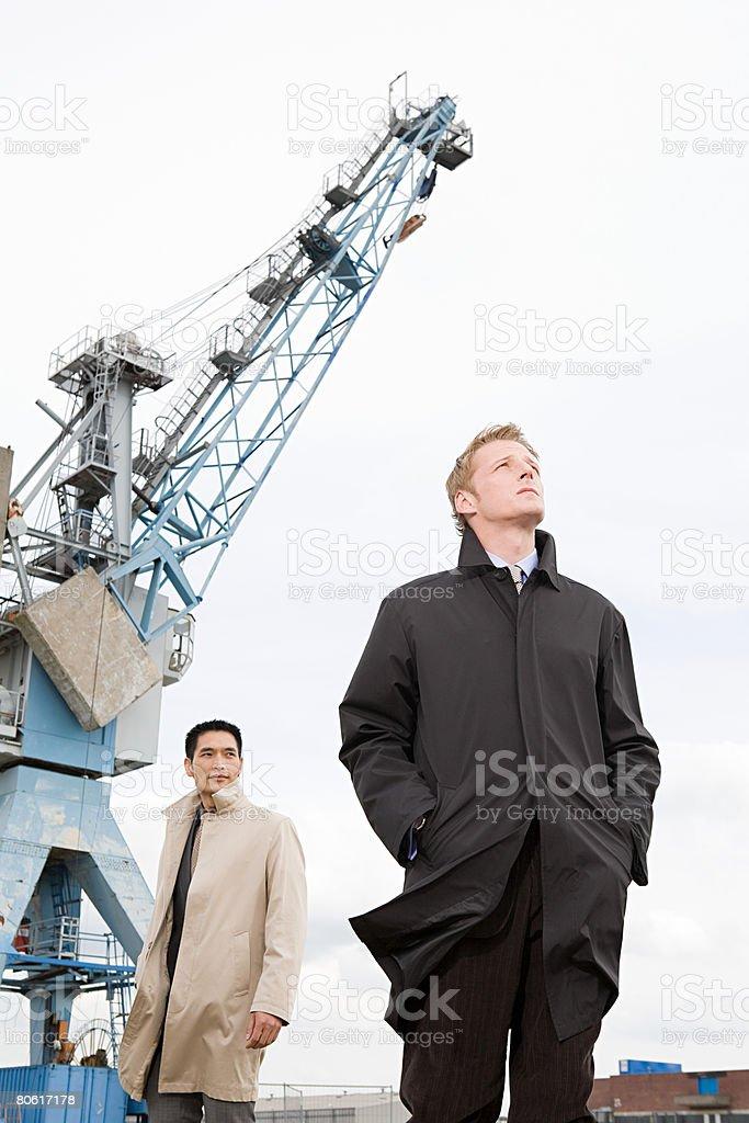 Zwei Geschäftsleute unter einem Kran Lizenzfreies stock-foto