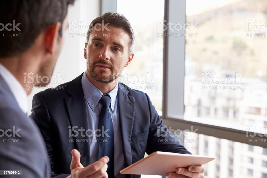 Two Businessmen Using Digital Tablet In Office Meeting royalty-free stock photo